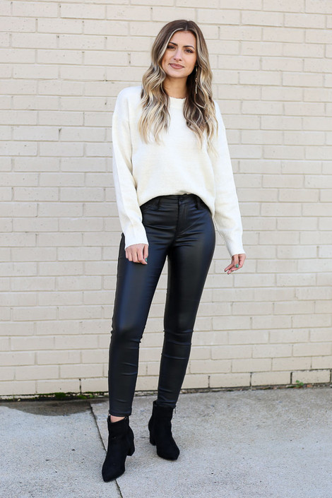 Model wearing the Mid Rise Faux Leather Skinny Jeans from Dress Up with knit sweater Front View