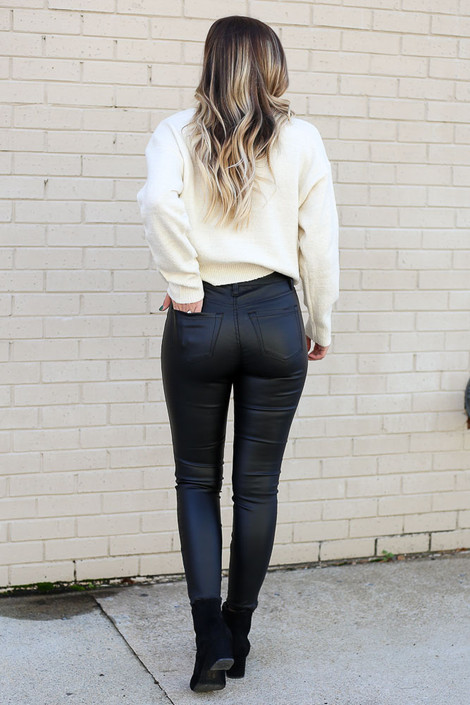 Model wearing the Mid Rise Faux Leather Skinny Jeans from Dress Up with knit sweater with ankle booties Back View