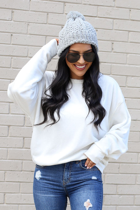 Model wearing the White Fuzzy Knit Pullover with pom pom beanie and distressed jeans Front View