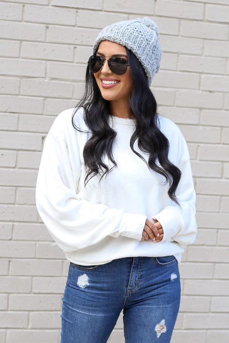 Dress Up Model wearing the  White Fuzzy Knit Pullover with pom pom beanie and distressed jeans Front View