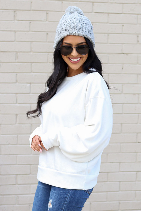 Model wearing the White Fuzzy Knit Pullover with pom pom beanie Side View