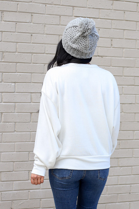 Model wearing the White Fuzzy Knit Pullover with pom pom beanie and distressed jeans Back View