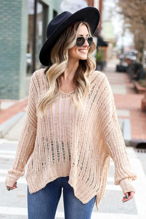 Model wearing the Blush Loose Ribbed Knit Sweater from Dress Up with wide brim hat and high rise jeans