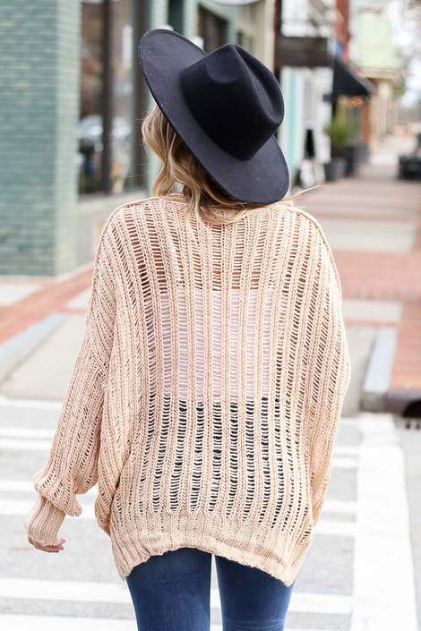 Model wearing the Blush Loose Ribbed Knit Sweater from Dress Up with wide brim hat and high rise jeans Back View