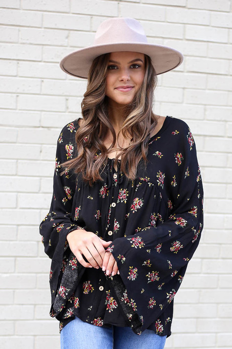 Black - Model from Dress Up wearing the Black Bell Sleeve Floral Babydoll Blouse with light wash jeans and wide brim hat Front View