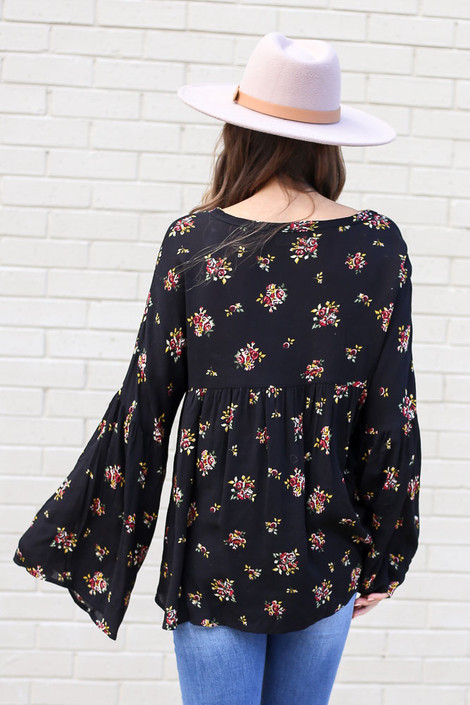 Model from Dress Up wearing the Black Bell Sleeve Floral Babydoll Blouse with light wash jeans and wide brim hat Back View