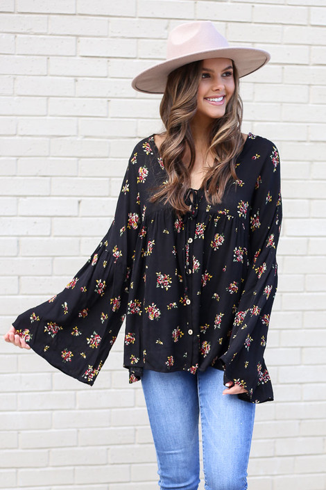 Model from Dress Up wearing the Black Bell Sleeve Floral Babydoll Blouse with light wash jeans Front View
