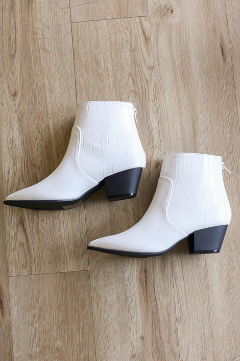 Flat Lay photo of the Crocodile Pointed Toe Booties in White on hardwood