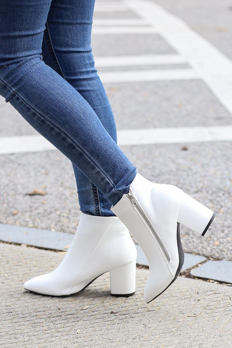 Model walking while wearing the Block Heel Ankle Booties from Dress Up