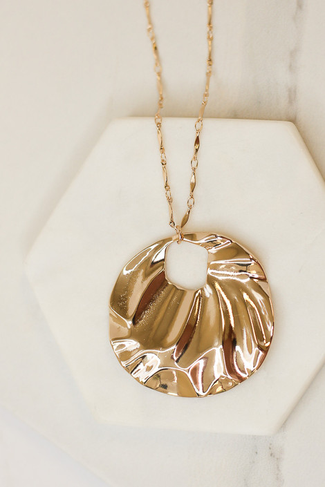 Flat Lay of Gold Hammered Pendant Necklace from Dress Up Boutique