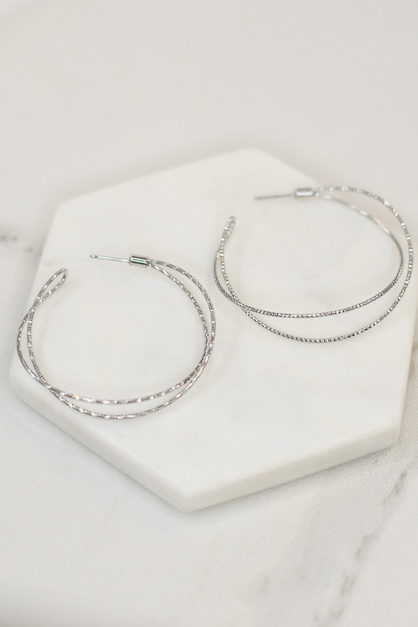 Flat Lay of Silver Textured Open Hoop Earrings from Dress Up