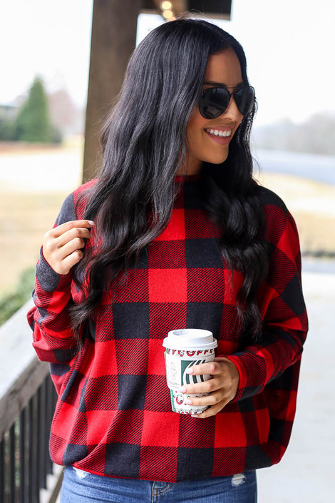 Model wearing the Red Buffalo Plaid Oversized Off the Shoulder Tunic with Starbucks Cup from Dress Up Front View