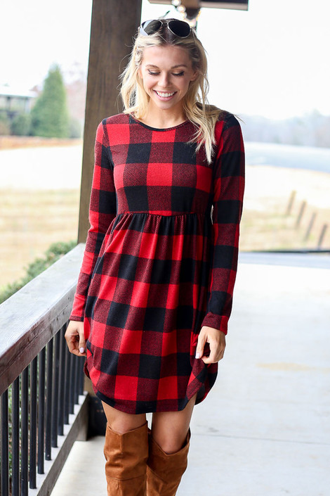 Model wearing the Buffalo Plaid Babydoll Dress from Dress Up in Red with tan over the knee boots Front View