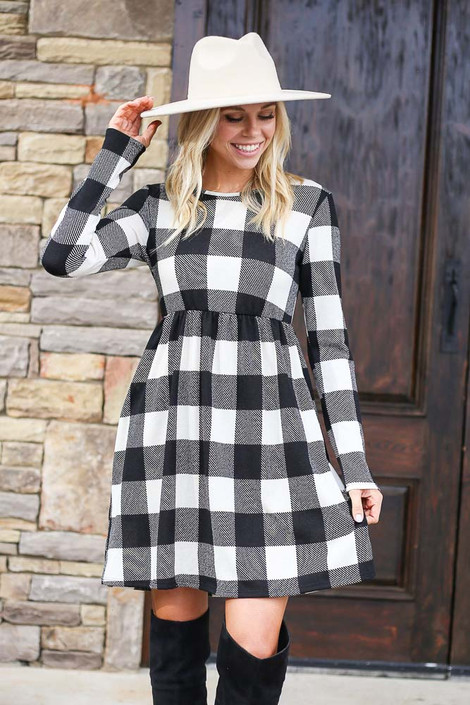 Model from Dress Up wearing the Buffalo Plaid Babydoll Dress in Ivory with black over the knee boots Front View