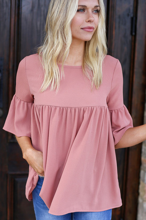 Close up of a model wearing the Ruffle Sleeve Babydoll Blouse in Marsala
