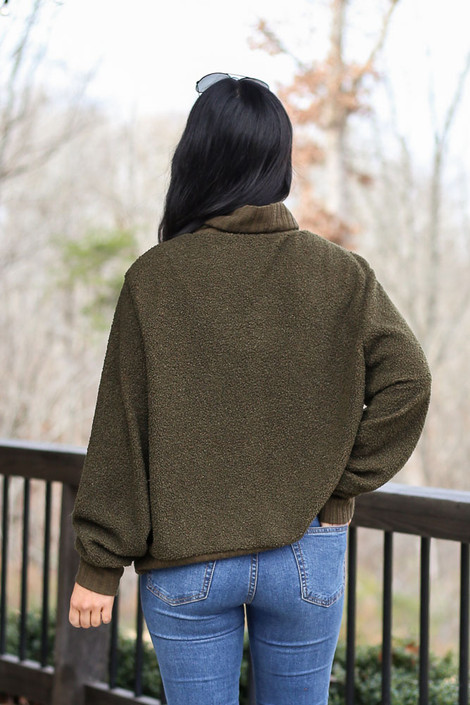 Model wearing the Teddy Sherpa Turtleneck Sweater from Dress Up in Olive Back View