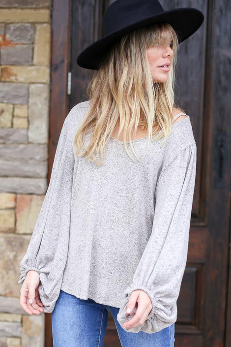 Model wearing the Heather Grey Brushed Knit Balloon Sleeve Top with light was skinny jeans and wide brim hat Front View