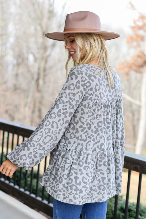 Model wearing the Grey Leopard Tiered Babydoll Tunic with wide brim hat and high rise jeans Back View
