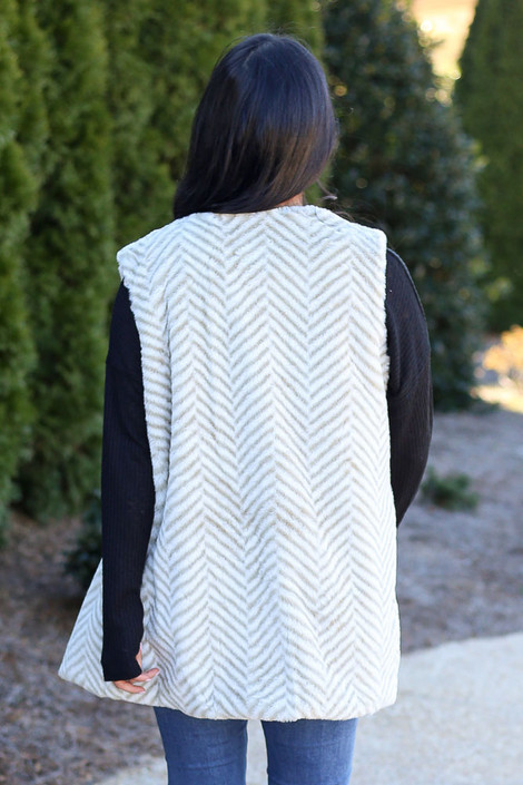 Model wearing the Chevron Faux Fur Vest with black long sleeve top and high rise jeans Back View
