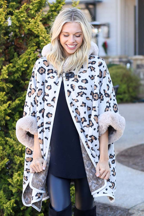 Model wearing the Fur Lined Leopard Knit Cape with skinny jeans and over the knee boots from Dress Up Front View