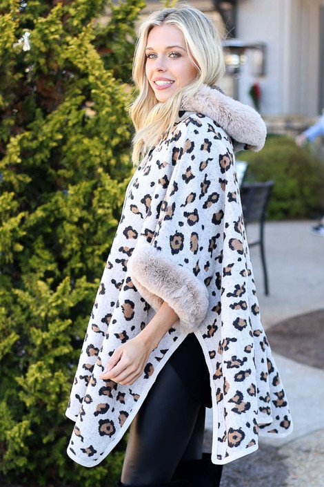 Model wearing the Fur Lined Leopard Knit Cape with skinny jeans and over the knee boots from Dress Up Side View