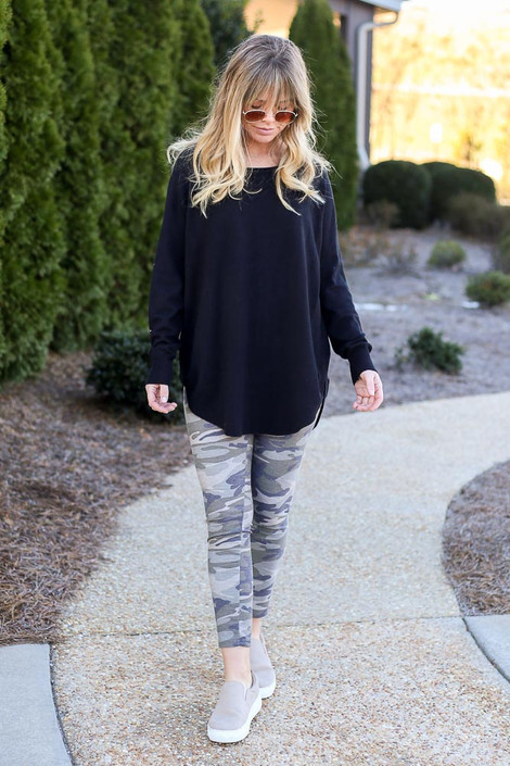 Model wearing the French Terry Camo Leggings with a black pullover and sneakers Front View