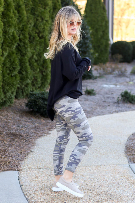 Model wearing the French Terry Camo Leggings with a black pullover and sneakers Side View