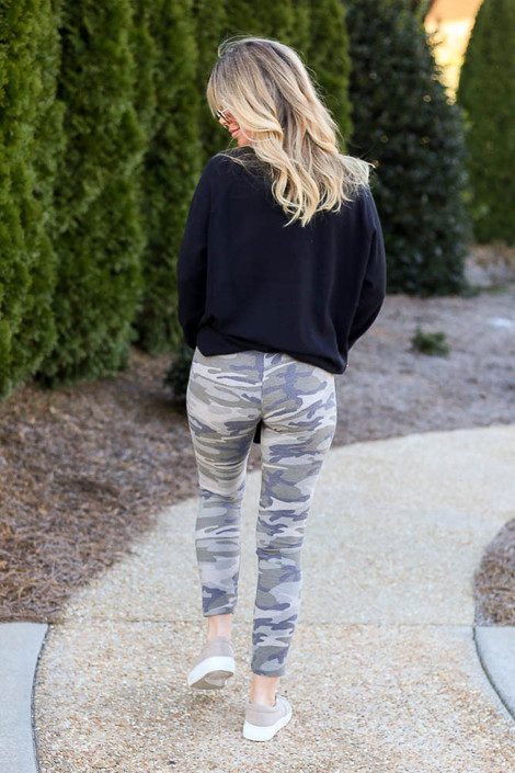 Model wearing the French Terry Camo Leggings with a black pullover and sneakers Back View