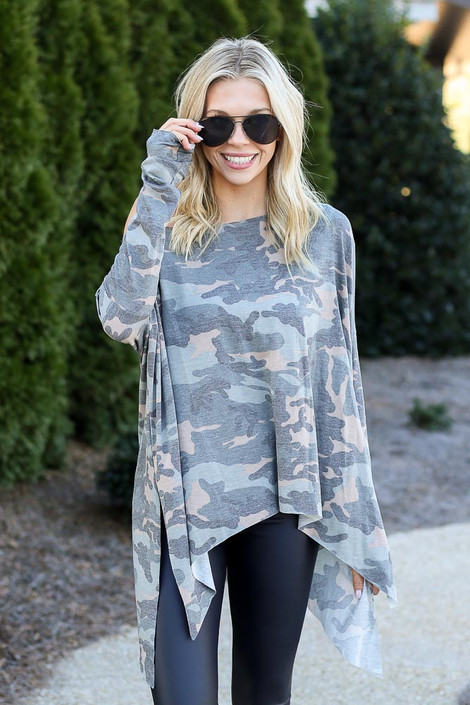 Model wearing the Camo Asymmetrical Raw Hem Top with dark wash jeans from Dress Up Front View