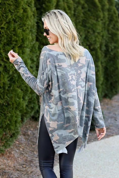 Model wearing the Camo Asymmetrical Raw Hem Top with dark wash jeans from Dress Up Back View
