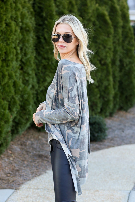 Model wearing the Camo Asymmetrical Raw Hem Top with dark wash jeans from Dress Up Side View
