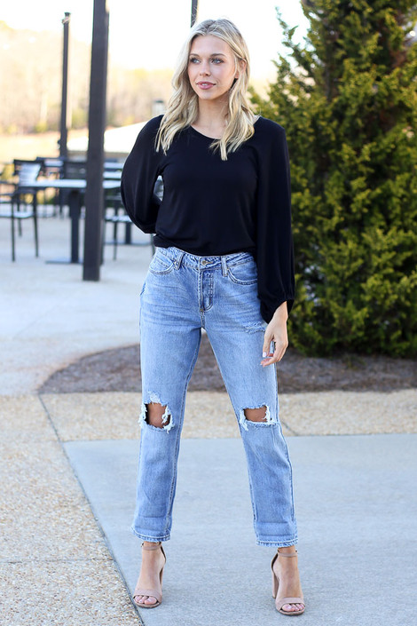 Model wearing the High Rise Distressed Boyfriend Jeans with heels and black ribbed top from Dress Up Boutique Front View