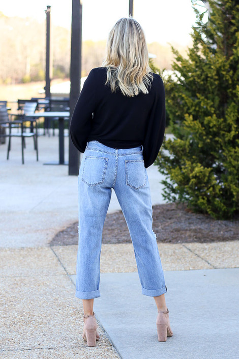 Model wearing the High Rise Distressed Boyfriend Jeans with heels from Dress Up Boutique Back View