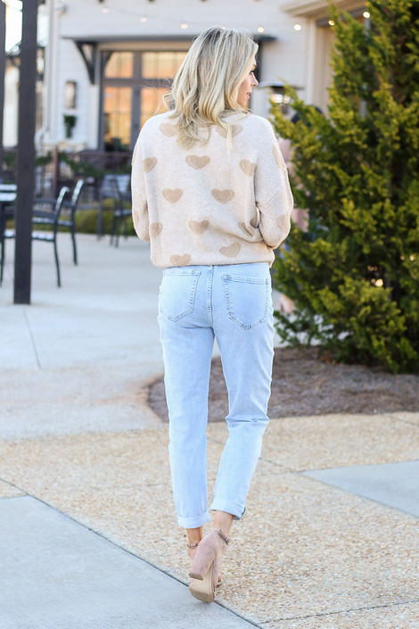 Model wearing the Light Wash High Rise Skinny Jeans with a knit sweater and heels from Dress Up Back View