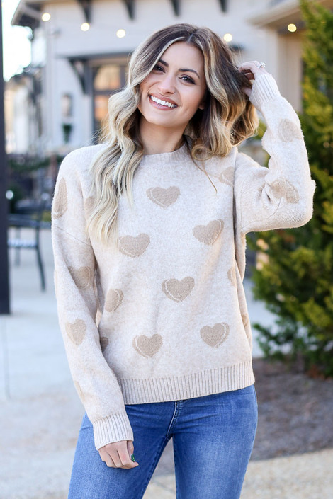 Model wearing the Taupe Eyelash Knit Heart Sweater with medium wash jeans from Dress Up
