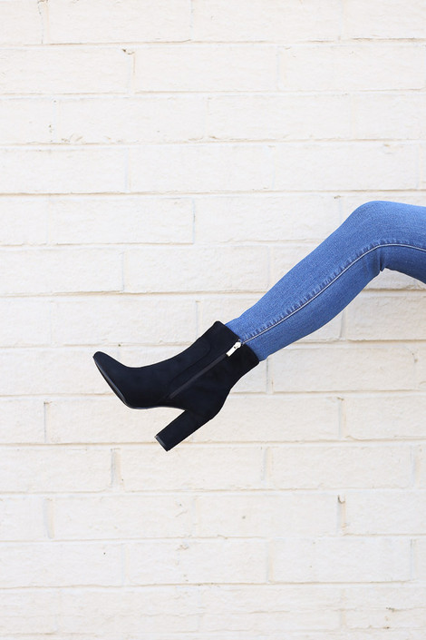 Model holding one leg up wearing the Block Heel Ankle Booties in Black
