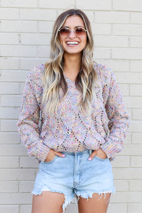 Model wearing the Rainbow Confetti Brushed Knit Sweater with denim shorts