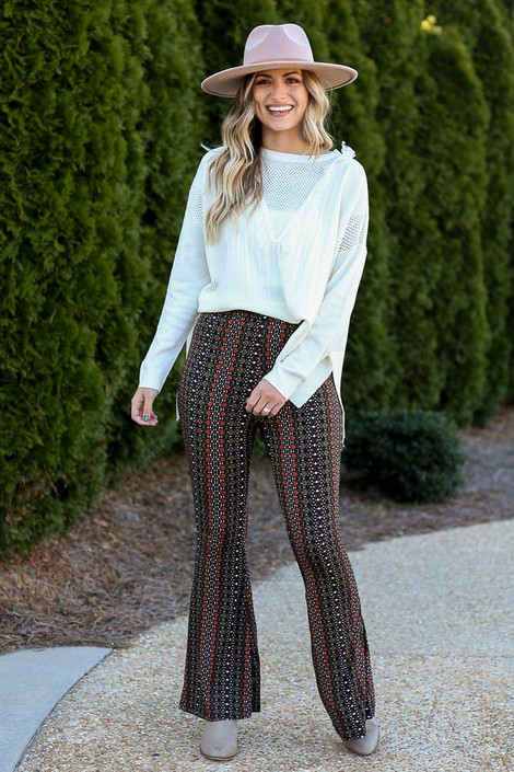 Model wearing the Print Knit Bell Bottom Pants with a white sweater and taupe booties
