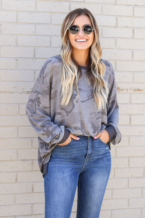 Model wearing the Oversized Lightweight Knit Pullover tucked into medium wash jeans