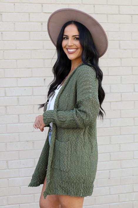 Model wearing the Popcorn Knit Sweater Cardigan in Olive from Dress Up Side View