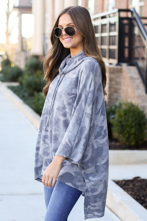 Model wearing the Grey Brushed Knit Cowl Neck Camo Poncho with high rise jeans from Dress Up Side View