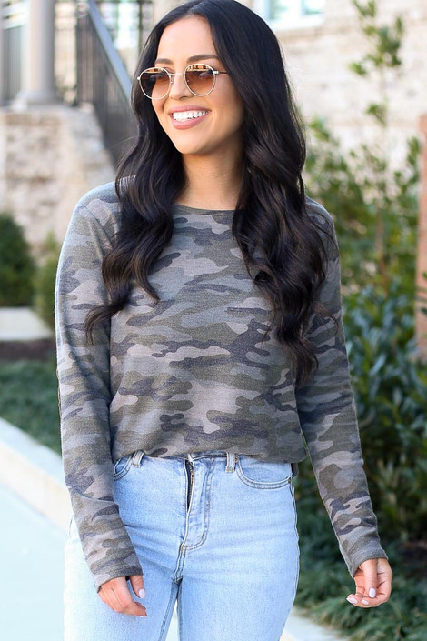 Model wearing the Elbow Patch Camo Top with high rise light wash jeans from Dress Up Boutique  Front View