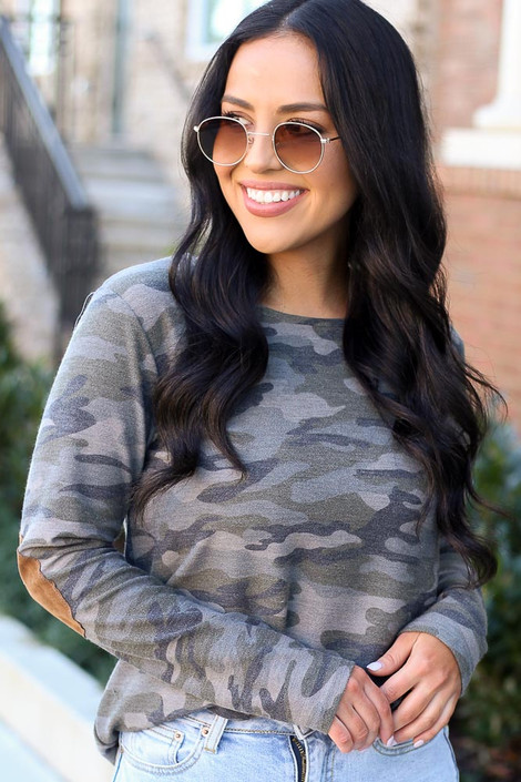 Model wearing the Elbow Patch Camo Top with high rise light wash jeans from Dress Up