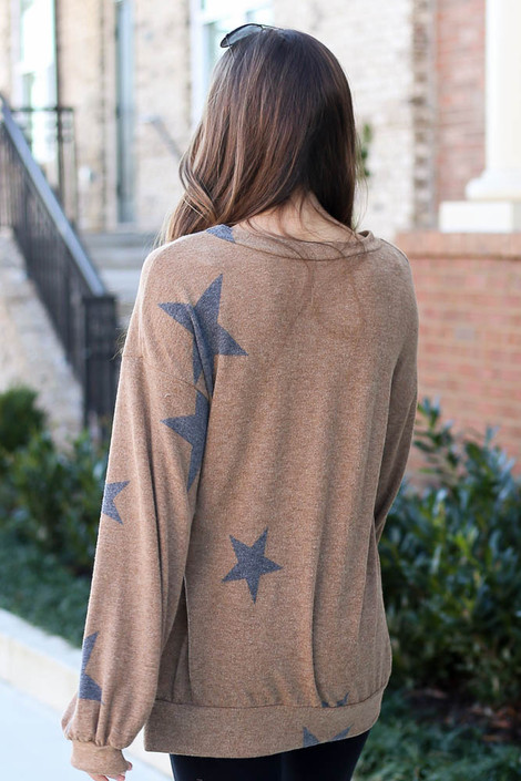 Model wearing the Taupe Star Brushed Knit Oversized Pullover with high rise leggings from DressUp Back View. Model wearing a star sweatshirt
