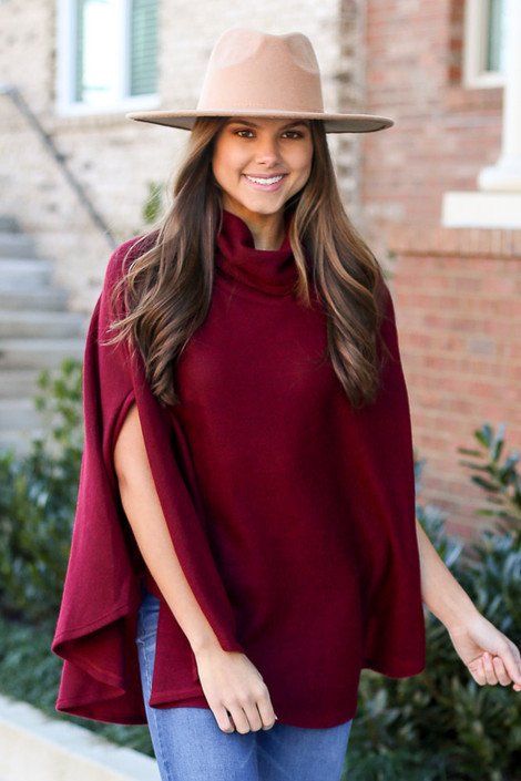 Model wearing the Brushed Knit Cowl Neck Oversized Poncho in Burgundy with medium wash jeans from Dress Up Front View. Wide Brim Fedora Hat in tan.