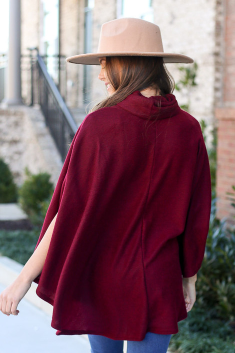 Model wearing the Brushed Knit Cowl Neck Oversized Poncho in Burgundy with medium wash jeans from Dress Up Back. Wide Brim Fedora Hat in tan.