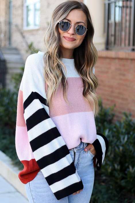 Multi - Model wearing the Oversized Color Block Knit Sweater with light wash denim jeans