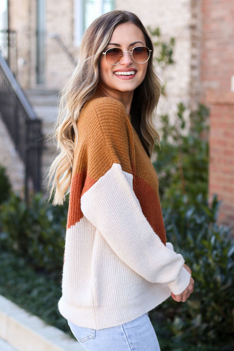 Model wearing the Color Block Sweater in Camel with high rise jeans from Dress Up Side View