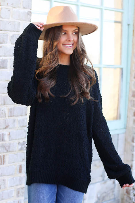 Model wearing the Popcorn Knit Oversized Top in Black with high rise skinny jeans and wide brim fedora from Dress Up Boutique