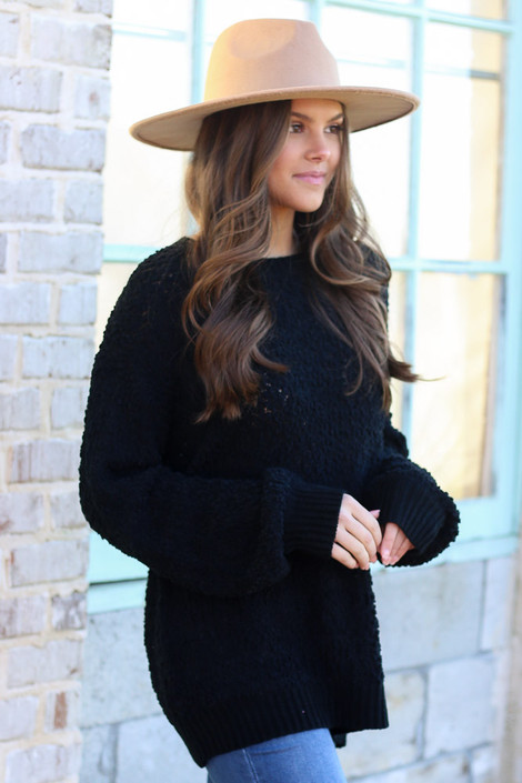Model wearing the Popcorn Knit Oversized Top in Black with high rise skinny jeans from Dress Up Boutique Side View